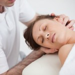Woman being massaging by the doctor while having the head turn i